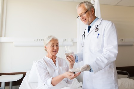doctor giving pills: doctor giving medication and water to senior woman at hospital ward Stock Photo