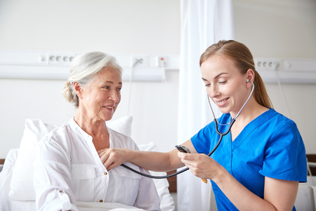 doctor or nurse with stethoscope visiting senior woman and checking her heartbeat at hospital ward
