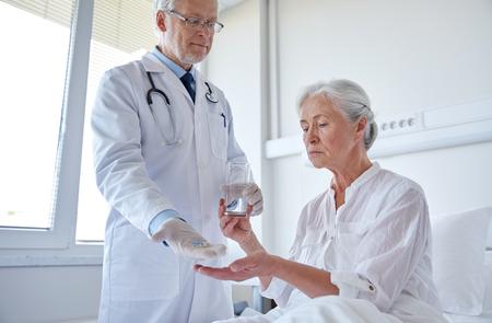 doctor giving medication and water to senior woman at hospital ward Stock Photo