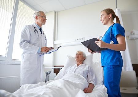 hospitales: médico y enfermera con portapapeles visitan mujer mayor paciente en sala de hospital