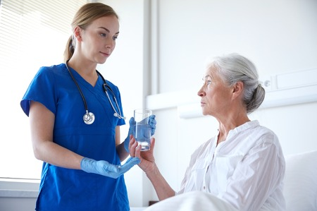 substance: nurse giving medication and glass of water to senior woman at hospital ward Stock Photo