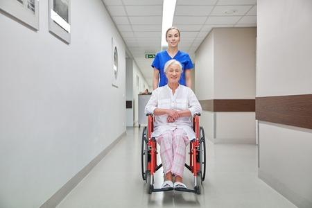 nurses: la medicina, la edad, el apoyo, la atención sanitaria y la gente concepto - enfermera tomando paciente mujer mayor en silla de ruedas en el pasillo del hospital