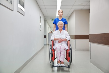 home healthcare: medicine, age, support, health care and people concept - nurse taking senior woman patient in wheelchair at hospital corridor