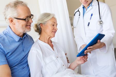 医学、年齢、医療、人々 コンセプト - 年配の女性、人および病棟でのタブレット pc のコンピューターを持つ医師