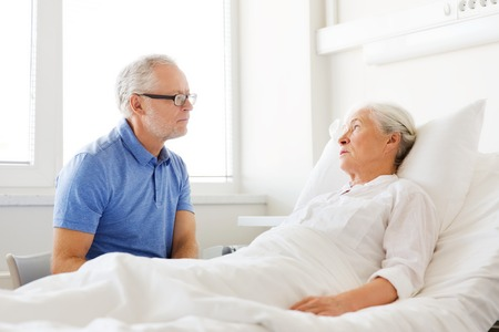 medicine, age, support, health care and people concept - happy senior man visiting and cheering his woman lying in bed at hospital ward Archivio Fotografico