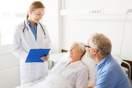 man in hospital bed: medicine, age, health care and people concept - senior woman, man and doctor with clipboard at hospital ward Stock Photo
