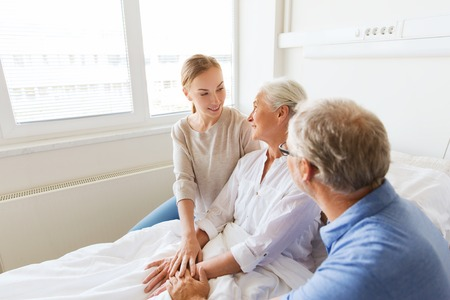man in hospital bed: medicine, support, family health care and people concept - happy senior man and young woman visiting and cheering her grandmother lying in bed at hospital ward Stock Photo