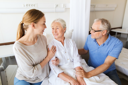 a hospital: medicine, support, family health care and people concept - happy senior man and young woman visiting and cheering her grandmother lying in bed at hospital ward Stock Photo