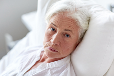 personen: geneeskunde, leeftijd, de gezondheidszorg en de mensen concept - senior vrouw patiënt liggend in bed in het ziekenhuis ward