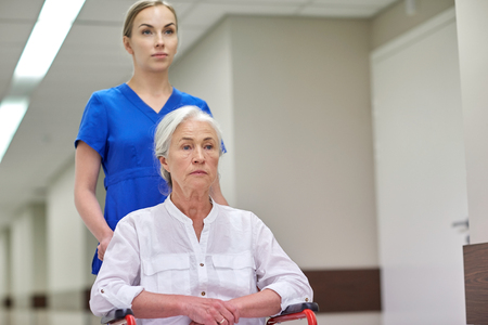 nurse: medicine, age, support, health care and people concept - nurse taking senior woman patient in wheelchair at hospital corridor