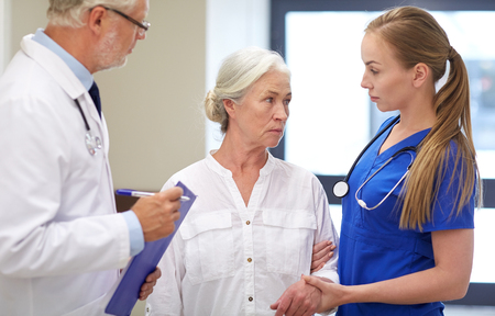 nursing aid: medicine, age, health care and people concept - male doktor with clipboard, young nurse and senior woman patient talking at hospital corridor Stock Photo