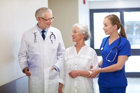 hospitales: la medicina, la edad, la salud y las personas concepto - médico masculino con el portapapeles, joven enfermera y paciente mujer mayor habla en el pasillo del hospital