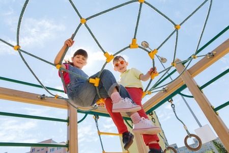 enfant qui joue: summer, childhood, leisure, friendship and people concept - group of happy kids on children playground climbing frame