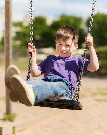 young boy smiling: summer, childhood, leisure, friendship and people concept - happy little boy swinging on swing at children playground