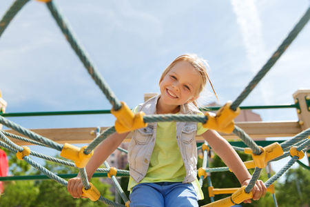 children playground: summer, childhood, leisure and people concept - happy little girl on children playground climbing frame