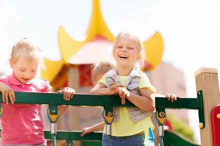 kids outside: summer, childhood, leisure, friendship and people concept - happy little girls laughing on children playground climbing frame Stock Photo