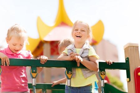 niños riendose: verano, la infancia, el ocio, la amistad y el concepto de la gente - niñas felices que ríen en el parque infantil columpio