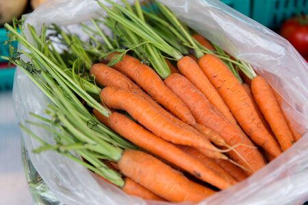 plastic: sale, harvest, food, vegetables and agriculture concept - close up of carrot in plastic bag at street market