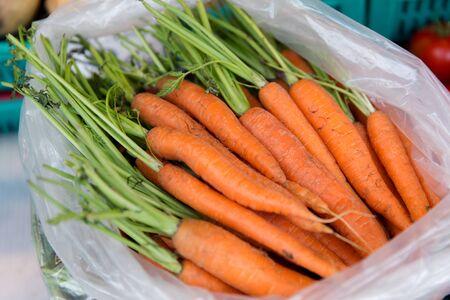 kunststoff: Verkauf, Ernte, Essen, Gemüse und Landwirtschaft Konzept - Nahaufnahme von Karotte in Plastiktüte auf der Straße Markt Lizenzfreie Bilder