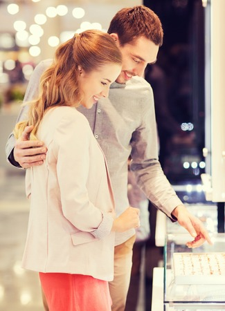 gold ring: sale, consumerism, shopping and people concept - happy couple choosing engagement ring at jewelry store in mall Stock Photo