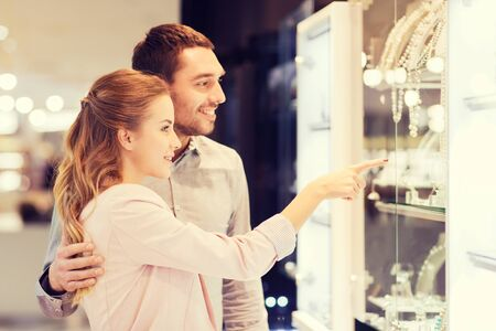hispanic couple: sale, consumerism and people concept - happy couple pointing finger to shopping window at jewelry store in mall