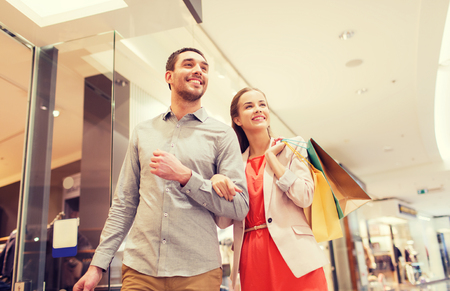 parejas: sale, consumerism and people concept - happy young couple with shopping bags walking in mall