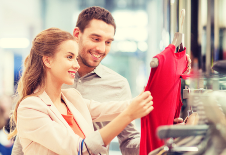 販売、消費者と人々 のコンセプト - ショッピング バッグ モールでドレスを選ぶと幸せな若いカップル