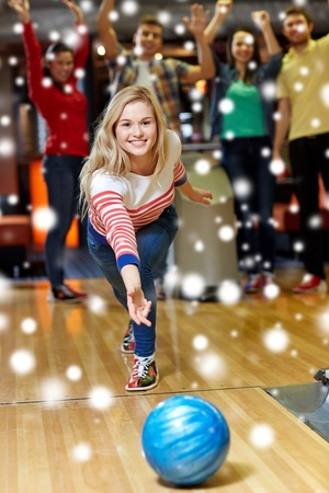 people: people, leisure, sport and entertainment concept - happy young woman throwing ball in bowling club at winter season Stock Photo