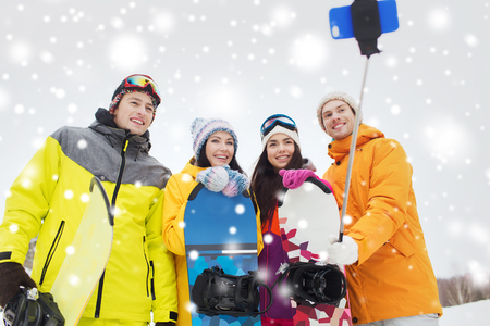 young people fun: winter sport, leisure, friendship, technology and people concept - happy friends with snowboards and smartphone taking selfie