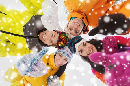 skiers: winter, leisure, friendship and people concept - happy friends standing in circle outdoors, showing thumbs up and and looking down Stock Photo