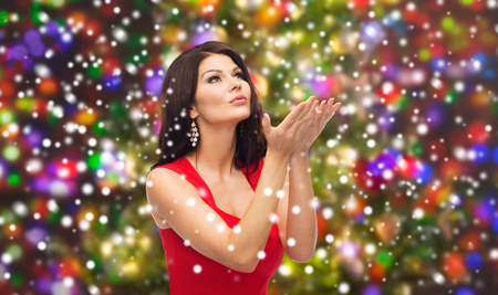 hot chick: people, holidays, christmas, magic and fashion concept - beautiful sexy woman in red dress sending blow kiss or making wish over lights background Stock Photo
