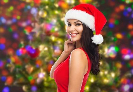 人、休日、クリスマス、お祝いコンセプト - サンタの帽子と赤いドレスの休日ライト背景の上で美しいセクシーな女性