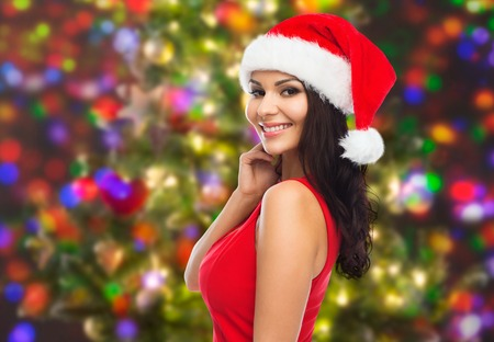 people, holidays, christmas and celebration concept - beautiful sexy woman in santa hat and red dress over holidays lights background