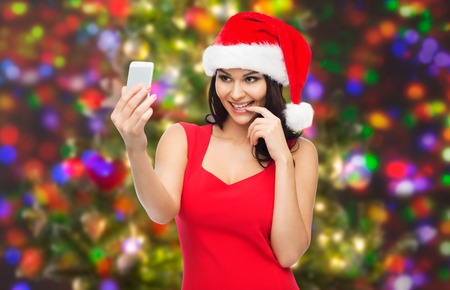 woman pose: people, holidays, christmas and technology concept - beautiful sexy woman in red santa hat taking selfie picture by smartphone