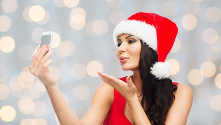 hot chick: people, holidays, christmas and technology concept - beautiful sexy woman in red santa hat taking selfie picture by smartphone and sending blow kiss to camera over holidays lights background