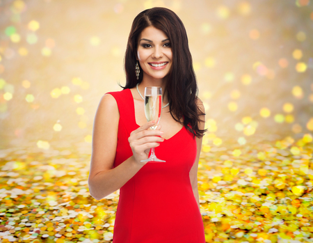 sexy dress: people, holidays, christmas and celebration concept - beautiful sexy woman in red dress with champagne glass over golden glitter or lights background