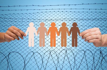Kriminalität, Gefängnis, Flüchtlings- und Menschen Konzept - vielpunkt Paar Hände, die Kette der Papierleute Piktogramm über blauen Himmel und Stacheldraht Hintergrund Standard-Bild - 49293830