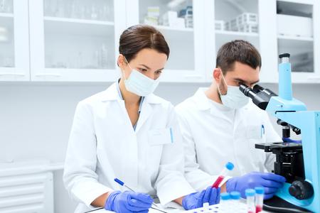 biologia: ciencia, química, la tecnología, la biología y la gente concepto - jóvenes científicos con tubo de ensayo y microscopio haciendo investigación en laboratorio clínico y tomar notas