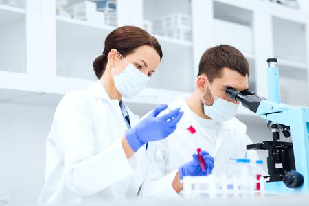biologia: la ciencia, la tecnología, la biología y el concepto de la gente - los científicos jóvenes con la pipeta, tubo de ensayo e investigación microscopio haciendo en el laboratorio clínico Foto de archivo