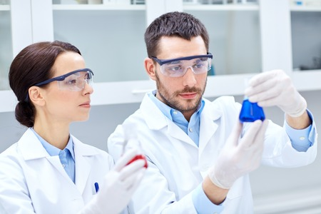 scientific research: science, chemistry, biology, pharmacy and people concept - young scientists with pipette and flask making test or research in clinical laboratory