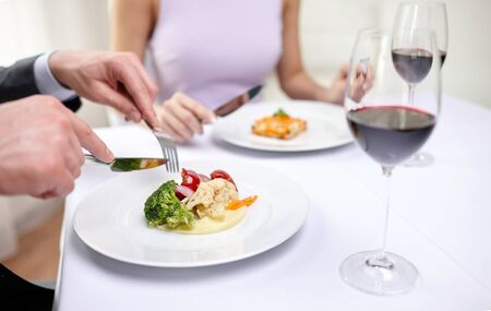 holiday food: restaurant, food, people, date and holiday concept - close up of couple eating appetizers at restaurant Stock Photo