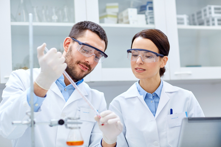 science, chemistry, technology, biology and people concept - young scientists with pipette and test tube making research in clinical laboratory Stock Photo