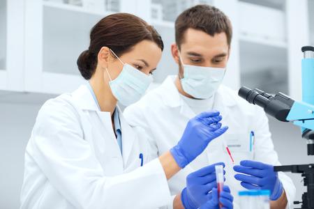 ciencia, química, la tecnología, la biología y la gente concepto - jóvenes científicos con la investigación de la pipeta y la toma de tubo de ensayo en laboratorio clínico Foto de archivo