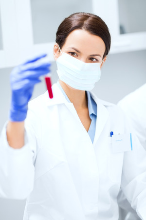 clinical laboratory: science, chemistry, biology, medicine and people concept - close up of young female scientist holding test tube with blood sample making research in clinical laboratory Stock Photo