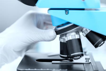 microscopio: la ciencia, la química, la biología, la medicina y la gente concepto - cerca de la mano en el guante de ajuste científico microscopio y en la investigación en laboratorio clínico