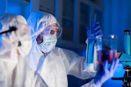 tubo de ensayo: la ciencia, la química, la biología, la medicina y el concepto de la gente - cerca de los jóvenes científicos con pipetas y frascos que hacen prueba o investigación en laboratorio clínico