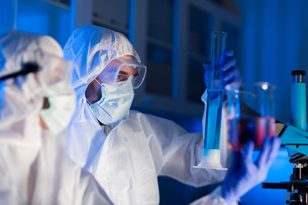 laboratory test: science, chemistry, biology, medicine and people concept - close up of young scientists with pipette and flasks making test or research in clinical laboratory