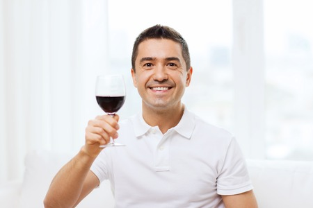 degustating: profession, drinks, leisure, holidays and people concept - happy man drinking red wine from glass at home