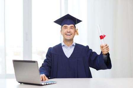 age: education, graduation, business, technology and people concept - happy adult student in mortarboard with diploma and laptop computer sitting at table home or office