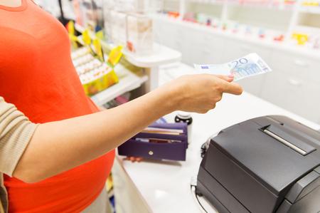 caja registradora: la medicina, la industria farmac�utica, la salud y las personas concepto - cerca de la mujer embarazada que da el dinero y la compra de medicamentos en la caja registradora de la farmacia Foto de archivo